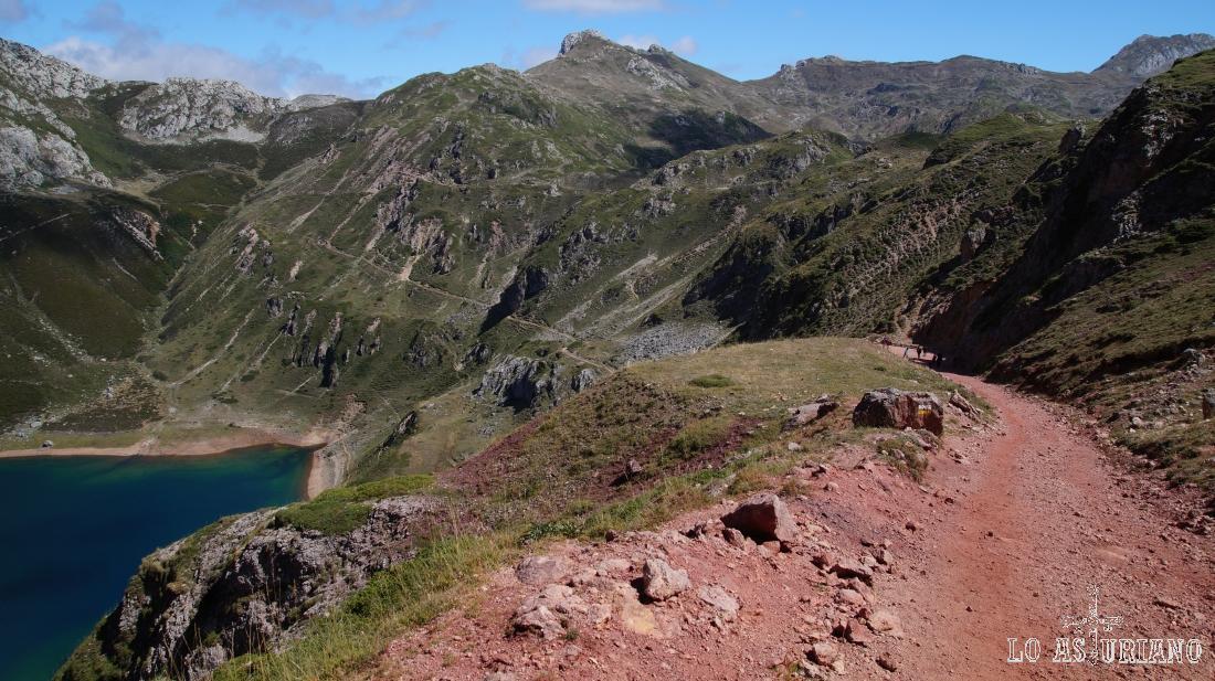 La pista rojiza, con restos de hierro, nos va bajando hacia el último de los lagos.