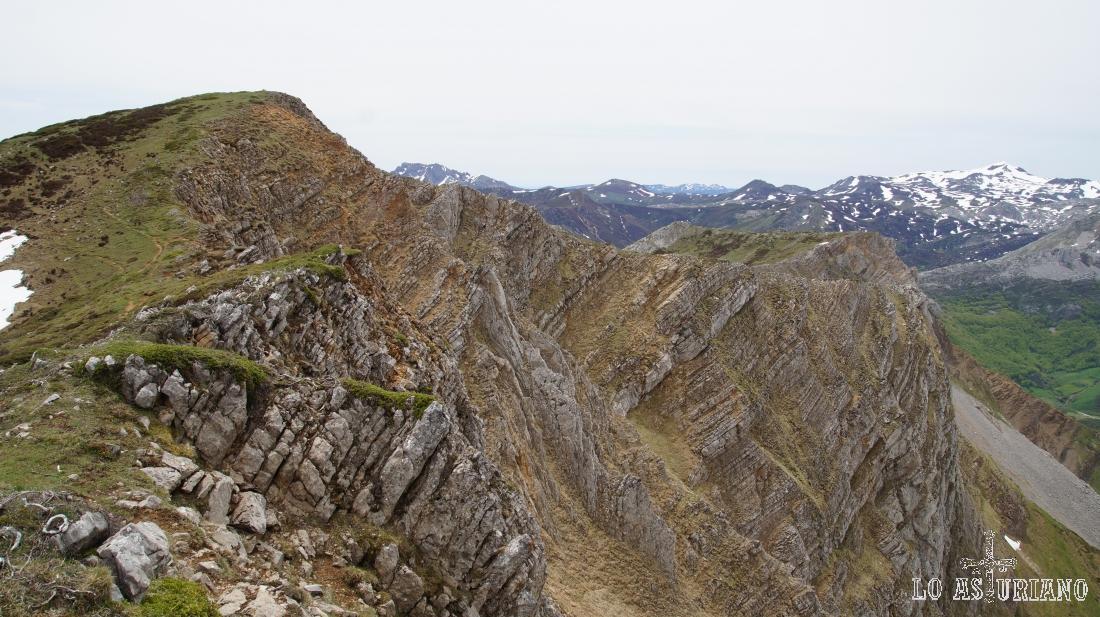 Paredes verticales y rocosas de la sierra de Robezu, con el pico Cornón, nevado, al fondo.