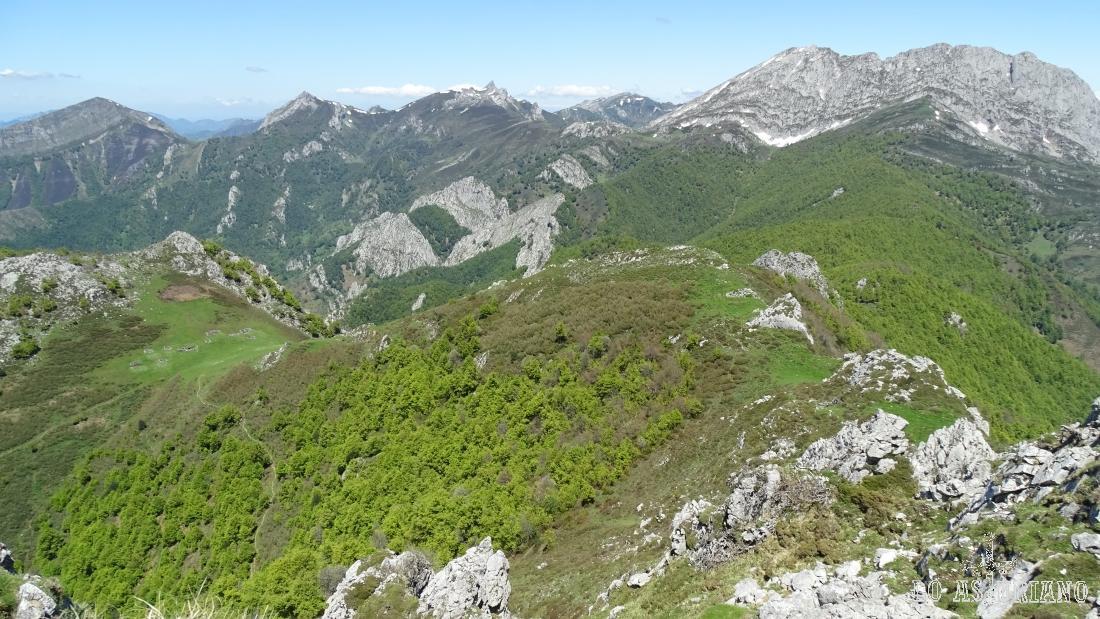 El Tiatordos, rodeado de cimas, praderas y verdes y primaverales bosques.