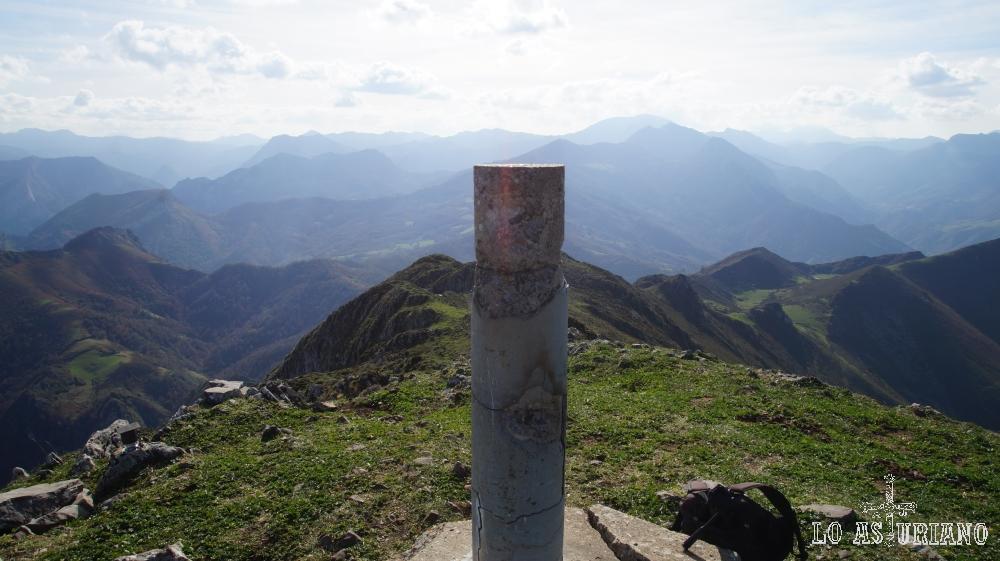 Pilón geodésico del pico Pierzu, y a contraluz, el mar de cimas del Parque Natural de Ponga.