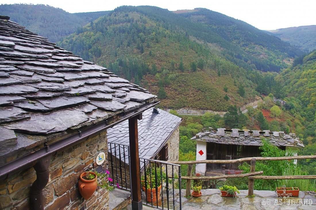 Disfrutamos un rato en este idílico Esquíos... En primer plano un tejado de pizarra. Enfrente el cabazo más antiguo de Asturias. Al fondo, el Pico dos Gamieiros, por cuyas laderas haremos parte de la ruta.