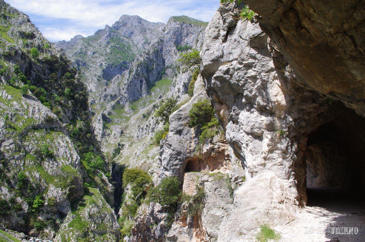 Túneles excavados en la roca y Cabeza Llambria al fondo, majestuoso, presidiendo la panorámica.