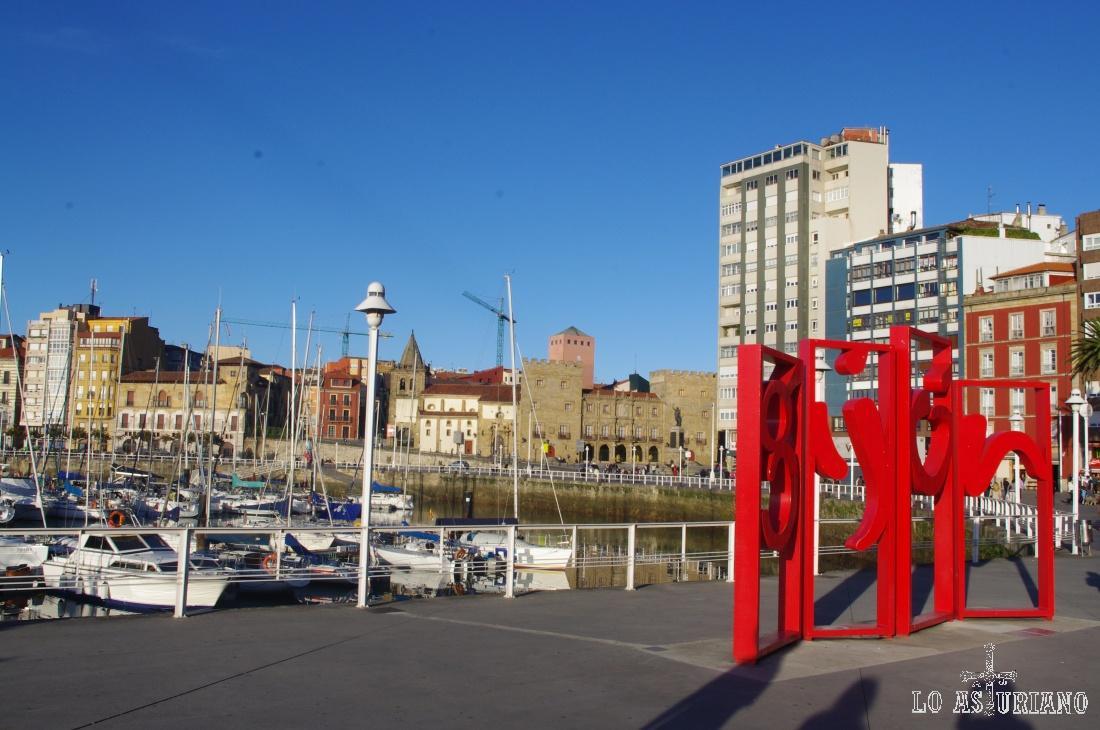 Desde la Calle Rodríguez San Pedro, el logo de Gijón, el puerto deportivo y el Palacio de Revillagigedo.