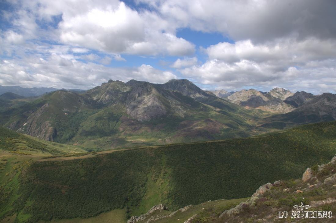 En tono verde, los montes de San Emiliano, y al fondo, los altos de La Farrapona y los Picos Albos somedanos. La vista es desde el cresterío del Ferreirúa.
