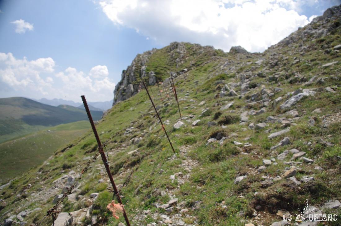 Para poder llegar a la zona más alta, debemos seguir la línea de la valla; muy pronto veremos las cimas del Muñón y de los Bígaros.