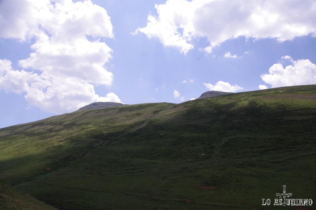 Asoma el Muñón y los Bígaros. Si subiésemos recto por esta pendientísima ladera, cosa que algunos hacen, llegarías a la laguna Llau (Chao) y luego podrías acceder a estas cimas por el paso del Muñón.