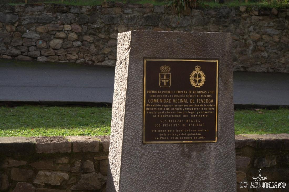 Bajo el tejo de la colegiata de La Plaza, está este letrero conmemorativo, sobre el premio de Teverga como Pueblo Ejemplar, el 26 de octubre del año 2013.