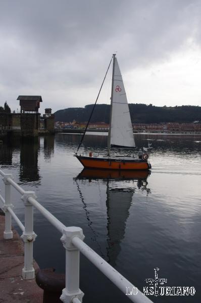 Barquito de vela en el puerto de San Esteban de Pravia. Al fondo, puedes ver antiguos lugares de carga de los barcos carboneros.
