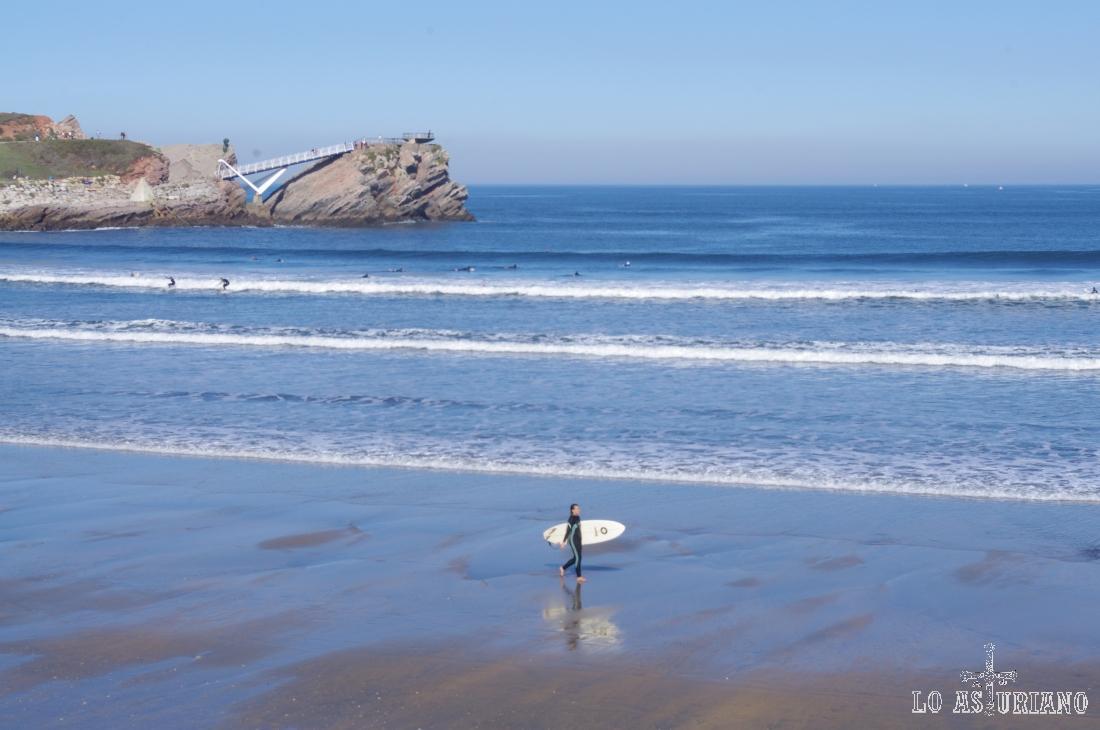 Surfero en la playa de Salinas, con el puente de la Gaviota y el mirador de la Peñona, al fondo.