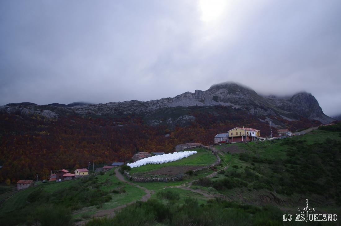 Casas de La Peral, con Peña Penouta y  Peña Canseco al fondo de la imagen.